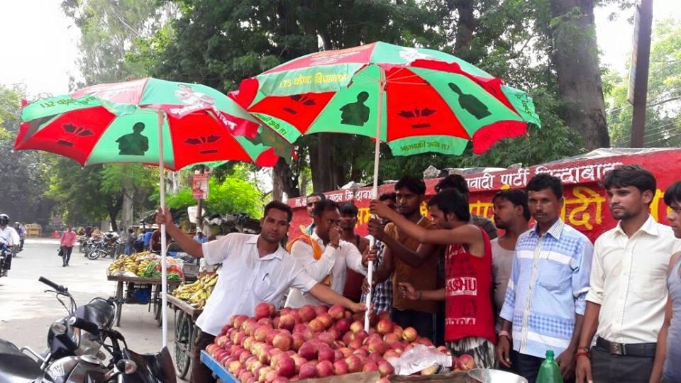 श्रीमती अपर्णा यादव की तरफ से कैण्ट विधान सभा क्षेत्र में पटरी दुकानदारों को छाते बांटे गये