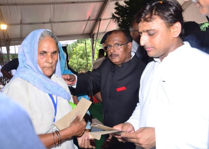 मुख्यमंत्री श्री अखिलेश यादव 19 जुलाई, 2016 को मुजफ्फरनगर में एक लाभार्थी महिला को सहायता प्रदान करते हुए।