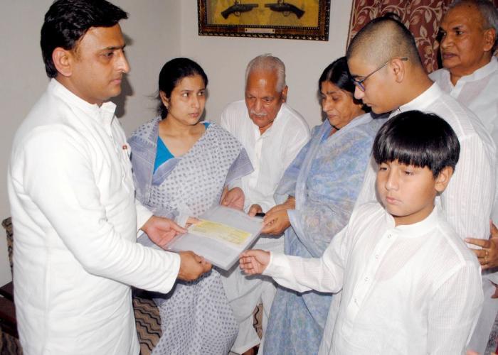 मुख्यमंत्री श्री अखिलेश यादव 13 जून, 2016 को मथुरा में शहीद पुलिस अधीक्षक को सांत्वना देने के बाद सहायता राशि का चेक प्रदान करते हुए।
