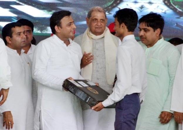 मुख्यमंत्री श्री अखिलेश यादव, सांसद श्री धर्मेंद्र यादव 2 सितम्बर, 2015 को जनपद इलाहाबाद में मेधावी छात्र को लैपटाॅप प्रदान करते हुए।