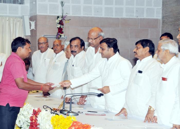 मुख्यमंत्री 19.09.2014 को श्रमिकोें के हितार्थ विभिन्न लाभकारी योजनाओं के उद्घाटन एवं लाभ वितरण समारोह में एक लाभार्थी को चेक प्रदान करते हुए।